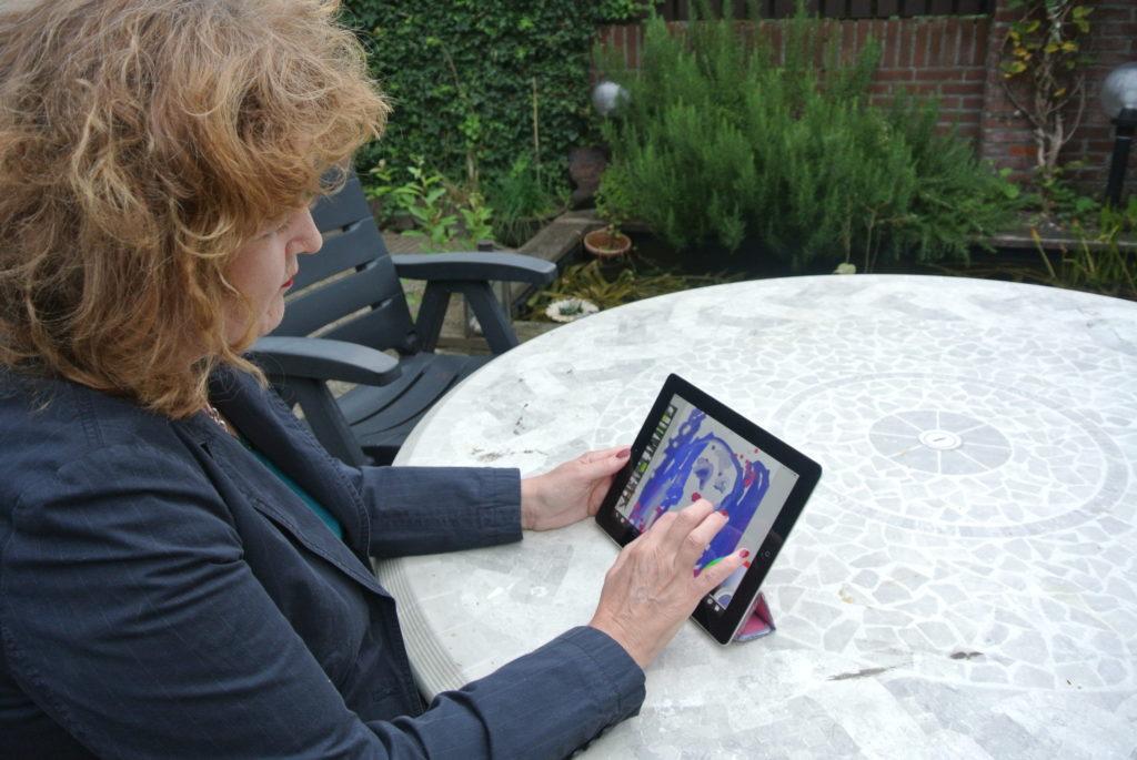 Rita Koolstra op haar eerste iPad in de tuin portretjes aan het schilderen